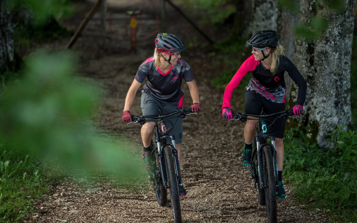 two women talking and enjoying their ride in the woods