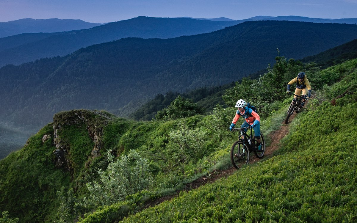two riders on a trail in the grassy mountains