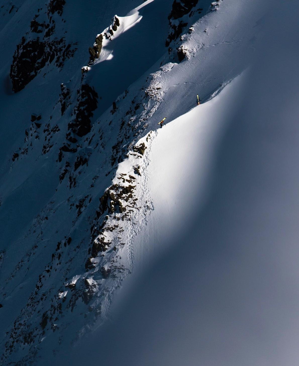 two skiers climbing on a ridge